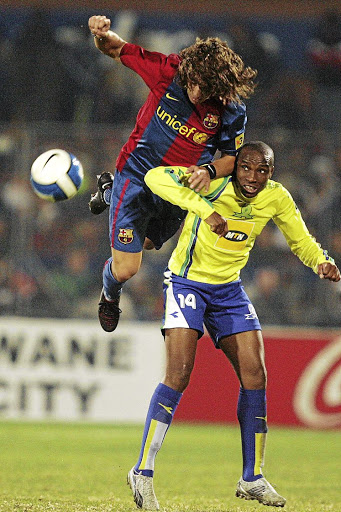 Retired Sundowns striker Surprise Moriri is challenged by Barcelona captain Carles Puyol in 2007.