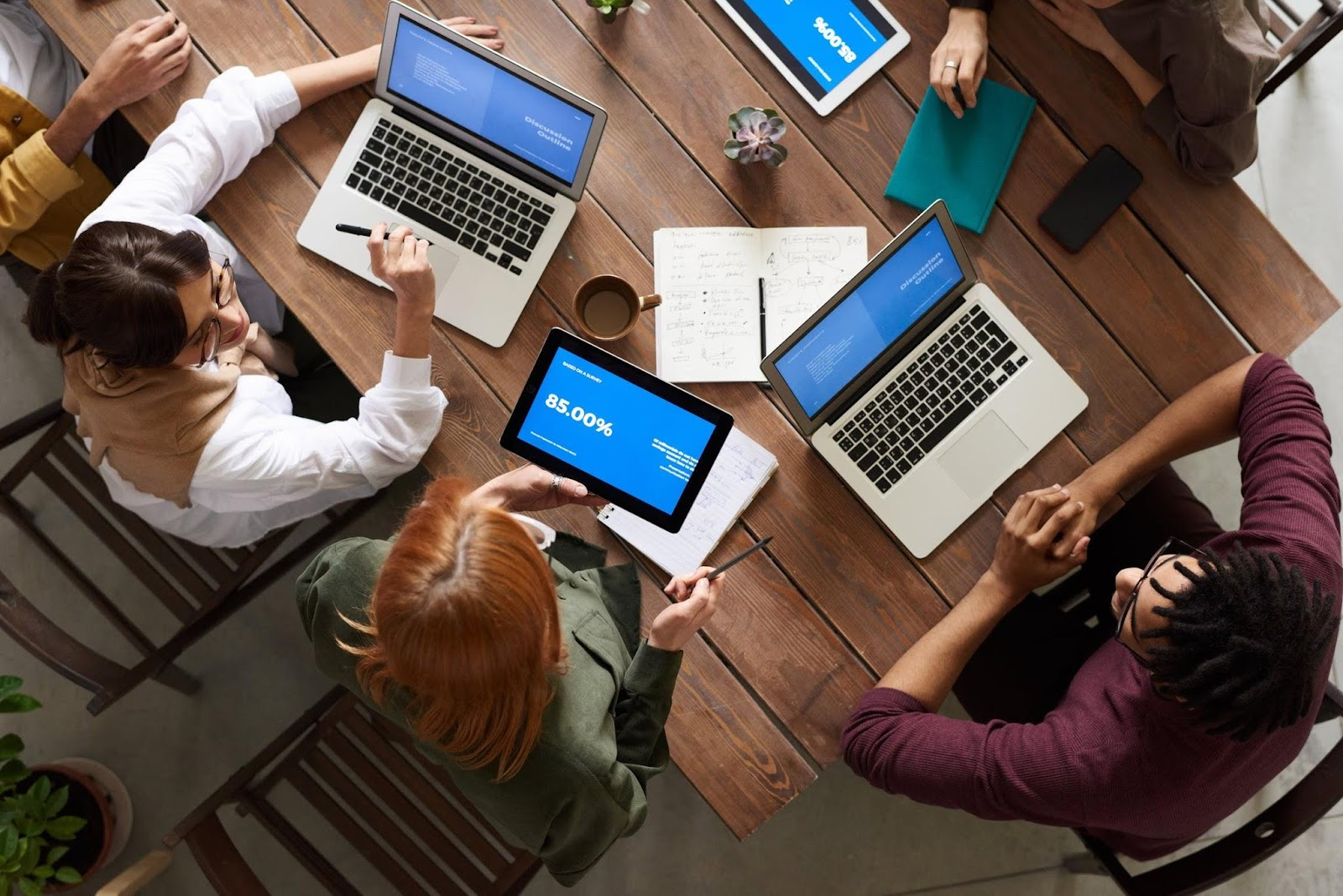top-view-photo-of-group-of-people-using-macbook-while-discussing-employee health and safety