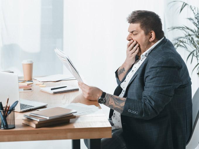 Übergewichtiger Mann sitzt an Schreibtisch – Übergewicht kann Altersdiabetes begünstigen