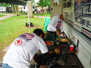 Photo: Day 43 Port Huron Pat and Jim Cooking spaghetti and bratwurst, and eggs under the canopy, in the rain