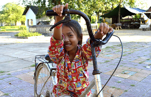 A shy girl on a bike in Vietnam was still very interested in meeting Western tourists.