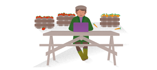 Éric, agriculteur, assis à l'extérieur, utilisant un ordinateur portable