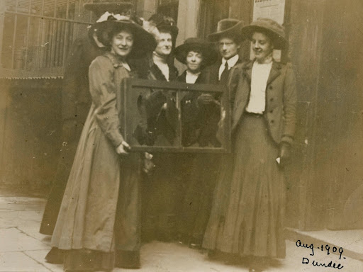 Suffragettes holding a broken window pane