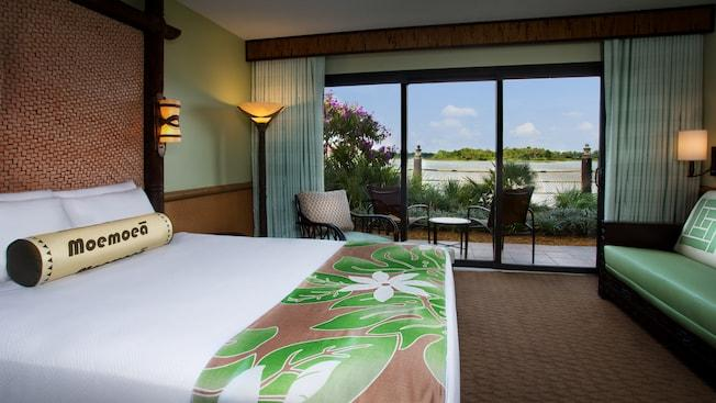 A queen bed and easy chair across from a daybed and, beyond, a patio and Seven Seas Lagoon