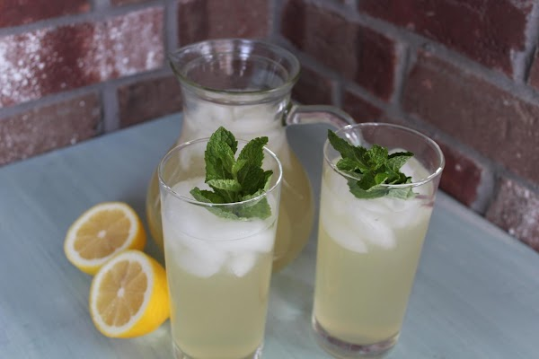 Fill glasses with ice. Add a sprig of mint or lemon balm and pour...