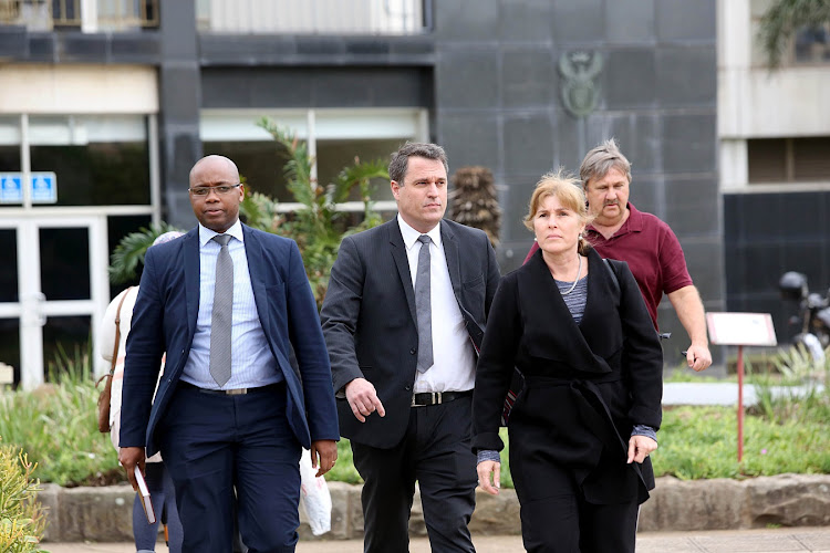 EnviroServ Group technical director Esme Gaumbalt and Chief Executive Dean Thompson along with a member of the EnviroServ legal team, stride away from the Durban Magistrate's court. They along with two other senior managers have been charged in their personal capacity for contravening the air quality legislation.