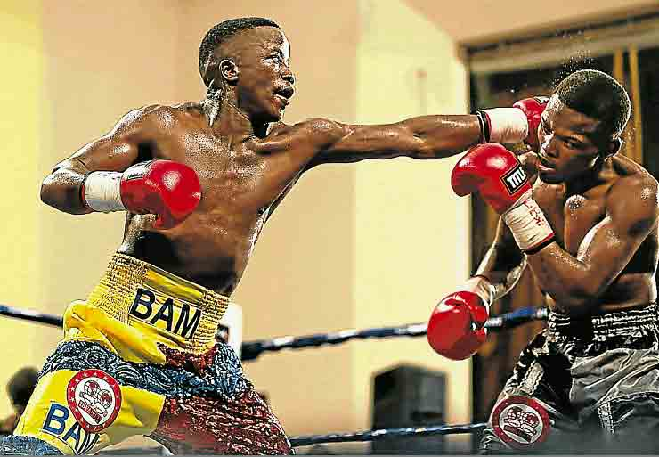 Sinethemba Bam smashes a left into the side of Phila Gola's retreating head during an earlier fight in his career.