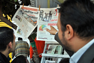 Photo: A man points to the newspaper cover of the beaten and stripped woman.