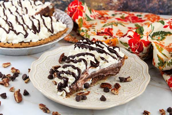 A Slice Of Chocolate Pecan Pie With Chocolate Pudding On A Plate.