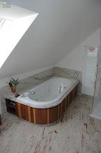 Photo: In amerikanischem Nussbaum, verarbeitet mit dem hellen Splintholz. Die runde Badewannenverkleidung ist abnehmbar montiert, dahinter verbirgt sich die Technik der Badewanne.