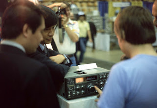 Photo: K1AR spins the tuning knob on the new TS-930 at Dayton 1982.  W2SQ in the background photographs W2PA taking this photo.