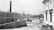 Tramo del muelle de poniente próximo a las instalaciones del Club de Mar. Al fondo, los barcos de guerra atracados en espigón. Verano de 1971.