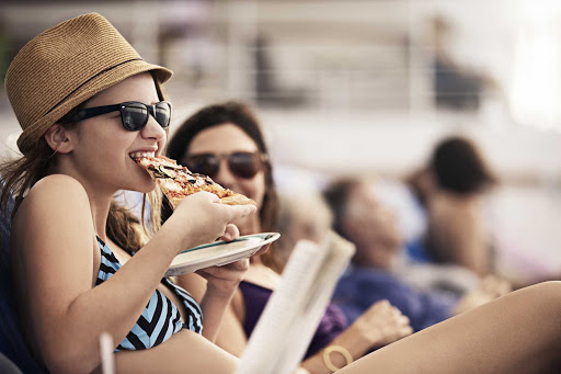 girl-eating-pizza-on-deck.jpg - A young woman eats pizza on the deck of a Princess cruise.