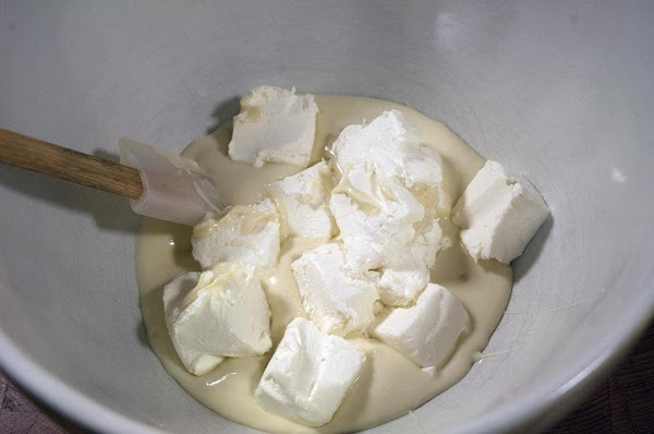 Add the melted chocolate to a large bowl, and then add the cream cheese.