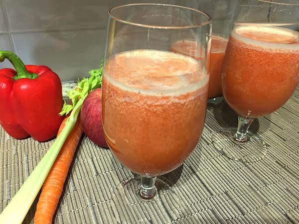Two Glasses Filled With Juice Sitting On A Beige Table Mat With A Carrot, Celery Rib, Red Pepper And Tomato.