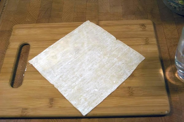 Lay an eggroll wrapper on a clean surface with one point facing you.