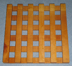 """Photo: This trivet started out as a, """"let me see what I can whip up for before the party this afternoon"""" project. It is cut from a single piece of pine using a dado cutting more than ½ the thickness from each side. This sort of repetitive incremental cutting is made much easier by Incra jigs. I used a jig that cuts each groove the same distance from its neighbor. So any error accumulates. The dado was a bit of a disappointment, since it does not leave a nice flat bottom. The chippers in the middle are not the same diameter as the edge cutters. A router bit would do a better job. The project ended being too much work, and not nice enough to let someone else have it. It is a little better than the projects that your kids bring home from school, that you cannot bear to throw out. It is functional, in pinch. Next time I will use a router, smaller grooves and nice wood, or go to Pier One."""