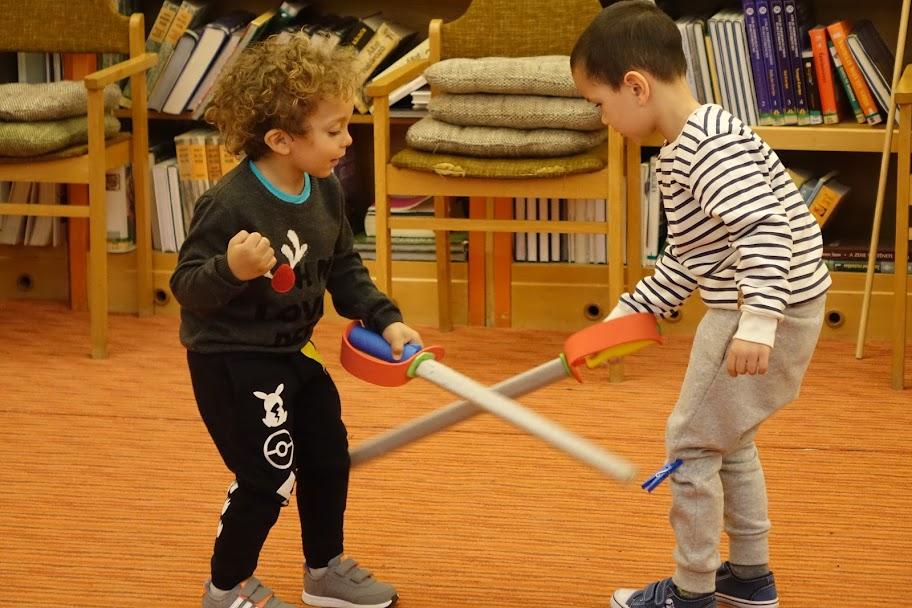 Karddal játszó gyerekek a könyvtárban