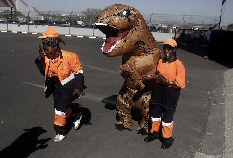 A person in a dinosaur costume plays around at Comic Con Africa 2018.