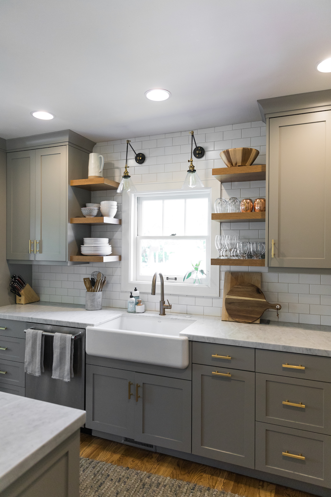 grey shaker kitchen with wood floating shelves installed above the farmhouse sink