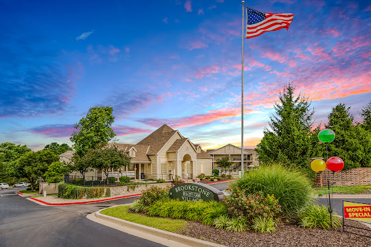 Brookstone Village apartment clubhouse with flag at dusk