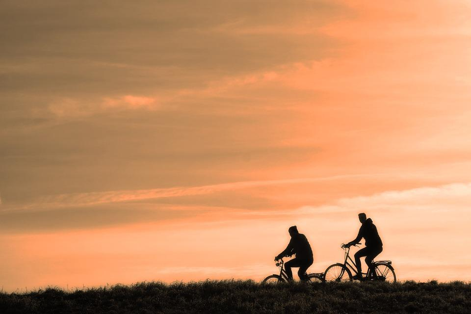 Two cyclists riding a bicycle