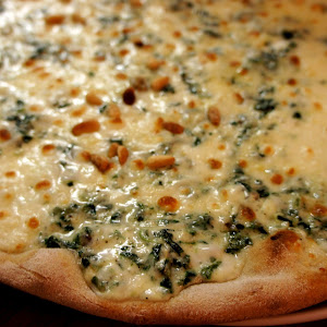 Signature pizza with fresh spinach, burrata cheese and pine nuts.