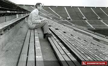 Photo: Wilkinson taking notes while sitting alone in Memorial Stadium.