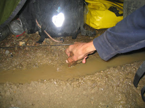 Photo: Digging a ditch in the tent in order to get the water away, and preventing the sleeping area from being soaked up