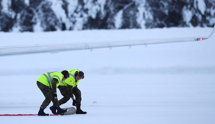 Workers roll out a red carpet for the Duke and Duchess of Cambridge to walk down on their arrival at Gardermoen Airport in Oslo, Norway, on Thursday.