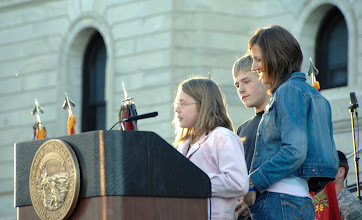 Photo: Brooke Lynn Thingvold, daughter of Lt. Col. Greg Thingvold, commander of the 2nd Battalion, 147th Assault Helicopter Battalion, speaks to her father, who is deployed in Iraq, via satellite at the Minnesota State Sesquicentennial Celebration. Thingvolds wife, Sara, and son, Derrick, are also pictured.