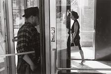 man komt binnen en vrouw loopt naar buiten bij ingang met glazen deuren