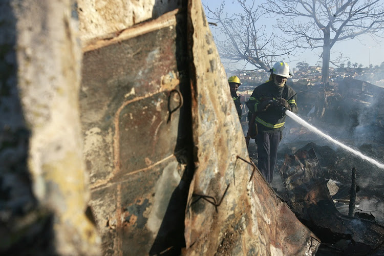 Firemen extinguish a shack fire in this file photo. Picture: DAILY DISPATCH/THEO JEPTHA