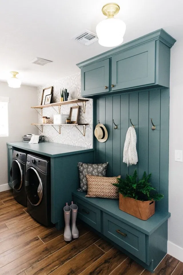 entryway laundry room mudroom with coat hooks, blue cabinets, small sitting bench, open shelving and washer dryer. wood floors and bright wall paint make the space feel inviting and open