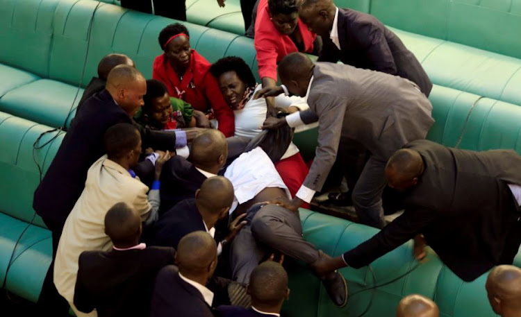 Ugandan opposition lawmakers fight with plain-clothes security personnel in the parliament while protesting a proposed age limit amendment bill debate to change the constitution for the extension of the president's rule, in Kampala, Uganda September 27, 2017.
