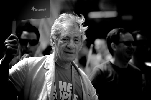 Actor Sir Ian McKellen walking among gay organisation Stonewall members, carrying a poster reading: