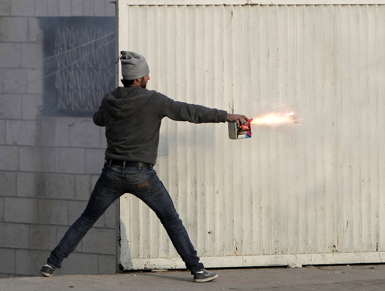 Photo: A Palestinian youth aims fireworks towards Israeli soldiers.