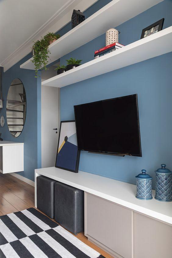 Sala com parede e acessórios decorativos azuis, rack e prateleiras brancas.