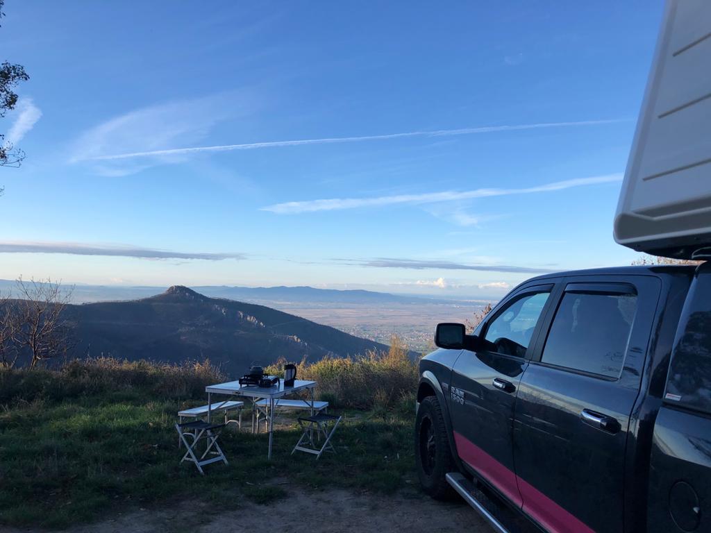 Auto und Dachzelt mit Camping Tisch und Stühlen vor bergigem Hintergrund