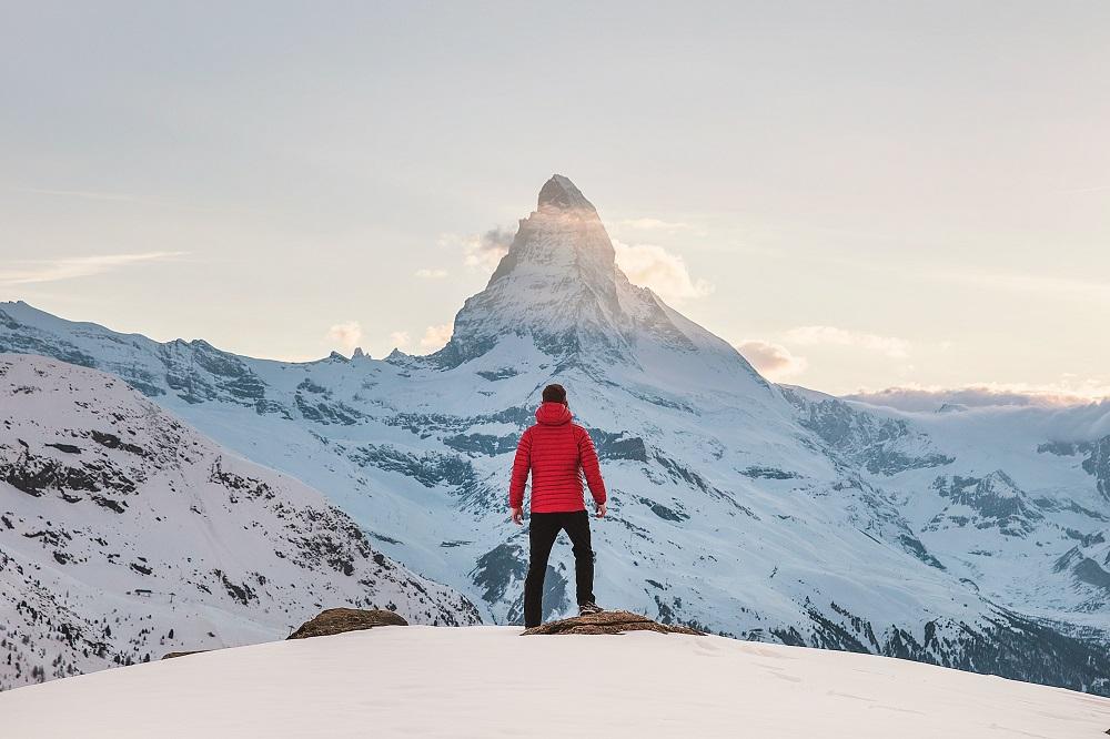 persona parada en la montaña viendo al pico