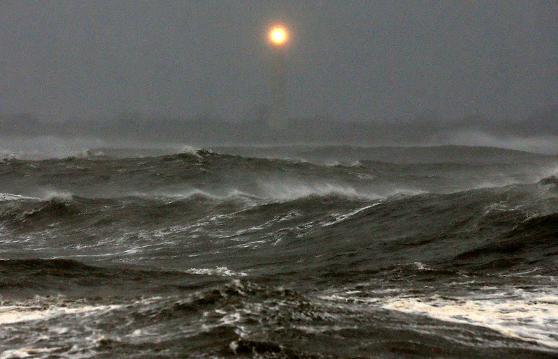 Photo: The Cape May Lighthouse can be seen as heavy surf from Hurricane Sandy pounds the shoreline.