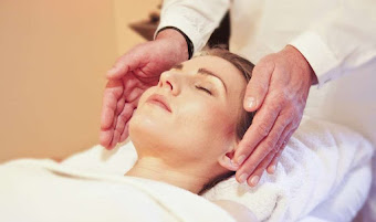 a lady lying down receiving a reiki treatment