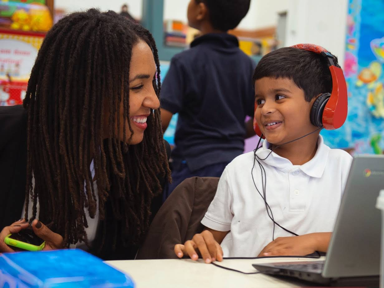 A woman leans over and smiles at a student listening on headphones with a Chromebook in use.