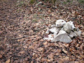 Photo: stone pile next to a path in the wood, in a small dip of the path - with snow this path would not be seen unless someone has gone along it before you ;-)