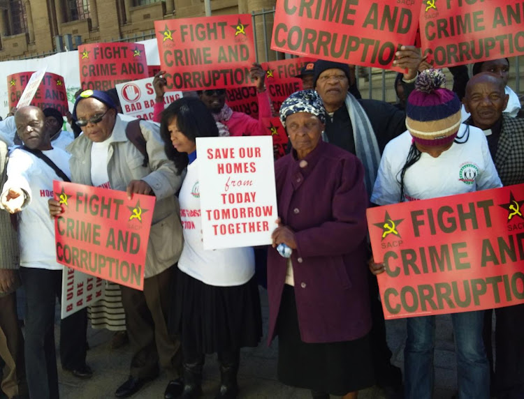 "Gogo Mviko, holding a poster that reads ""Save our homes"" joins a picket outside the High Court in Johannesburg."