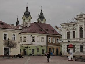 Photo: Opuszczamy Rynek. Ponad zabudowaniami widnieją wieże neoromańskiego kościoła pw. Przemienienia Pańskiego. Obiekt znajduje się w miejscu starej gotyckiej świątyni pw. Michała Archanioła, która doszczętnie spłonęła w 1782 roku i nie została odbudowana. W jej wnętrzu w roku 1417, król Władysław Jagiełło wziął ślub z Elżbietą Granowską. http://pl.wikipedia.org/wiki/Ko%C5%9Bci%C3%B3%C5%82_Przemienienia_Pa%C5%84skiego_w_Sanoku http://38500sanok.w.interia.pl/historia.htm