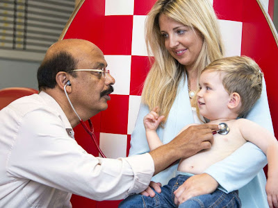 Dr Rajiv Sood checking the heart rate of a child at his consultant paediatric offices