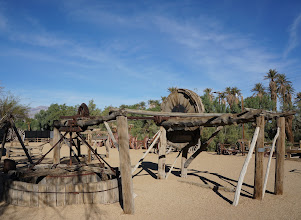 "Photo: An Arrastra is a primitive mill for grinding and pulverizing ore. The simplest form of the arrastra is two or more flat-bottomed drag stones placed in a circular pit paved with flat stones, and connected to a center post by a long arm. With a horse or mule providing power at the other end of the arm, the stones were dragged slowly around in a circle, crushing the ore. The word ""arrastra"" comes from the Spanish ""arrastre"", meaning to drag along the ground. Arrastras were suitable for use in small or remote mines, since they could be built from local materials and required little investment capital."