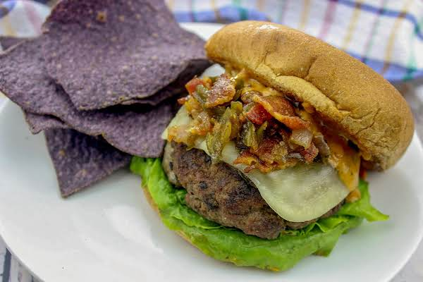 An All American Cajun Burger On A Plate With Tortilla Chips.