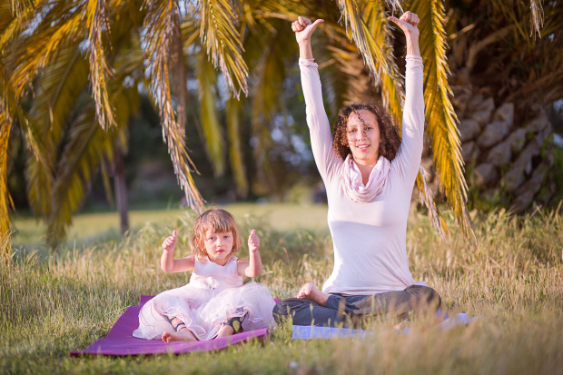 Mom and daughter sitting with fists up thumbs pointed inward